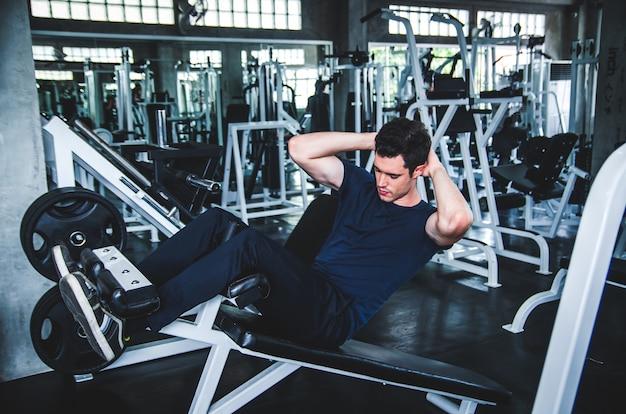 Homme exerçant travailler et flexion des muscles dans la salle de gym