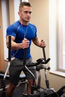 Homme exerçant sur vélo elliptique
