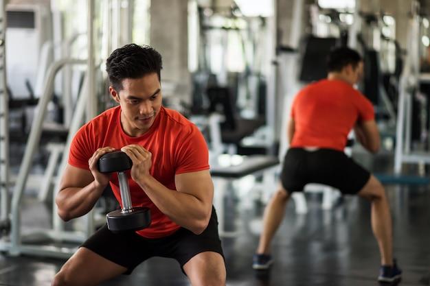 Homme, exercice, biceps, par, haltère, dans, gymnase