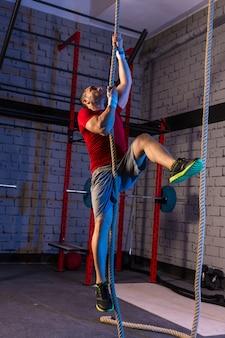 Homme d'exercice de corde d'escalade au gymnase