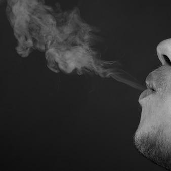 L'homme exhale de la fumée de cigarette de près, monochrome