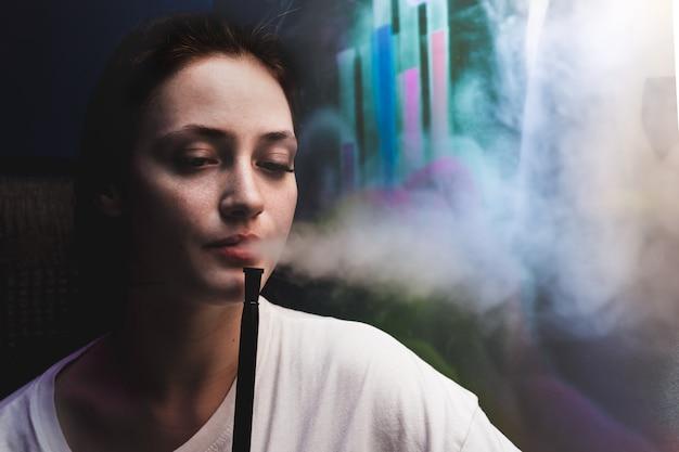 L'homme exhale de la fumée fille fume le narguilé
