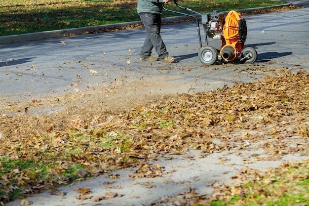 Homme d'exploitation nettoyer le trottoir avec un souffleur de feuilles en automne