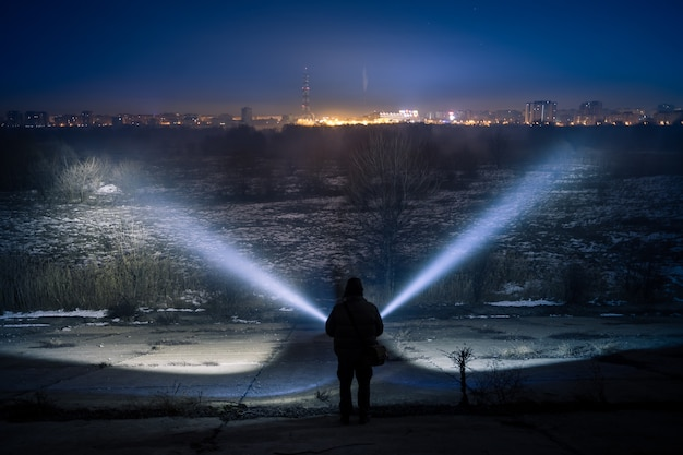 Homme explorant avec deux lampes de poche la nuit