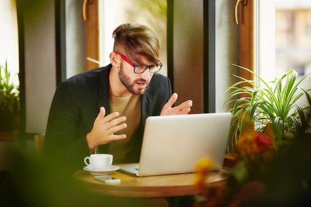 Homme expressif assis à un ordinateur portable au café
