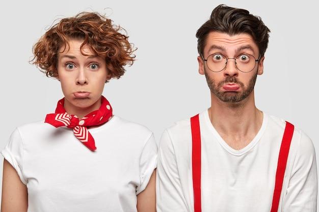 Homme expressif et femme en t-shirts blancs posant