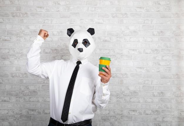 Homme expressif avec tête d'ours panda tenant une tasse de café