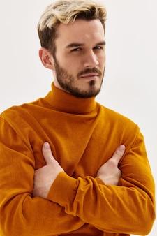 L'homme avec une expression méfiante a croisé ses mains devant lui studio de mode de style d'automne