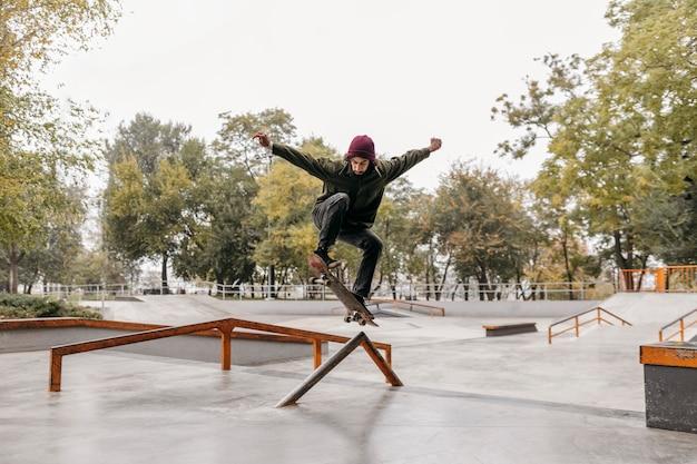 Homme à l'extérieur avec planche à roulettes dans le parc