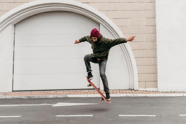 Homme à l'extérieur avec planche à roulettes dans la ville
