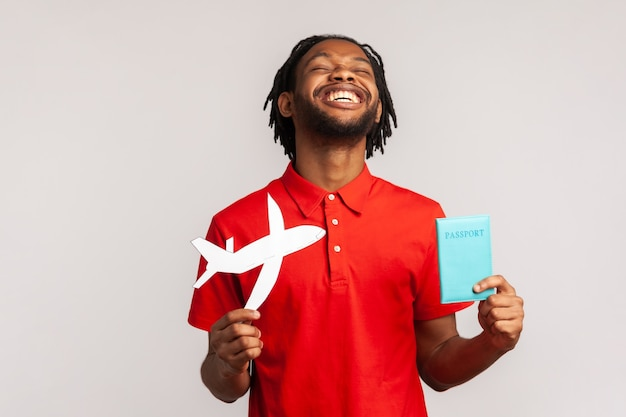 Homme extrêmement heureux tenant un passeport et un avion en papier, se réjouissant du voyage.