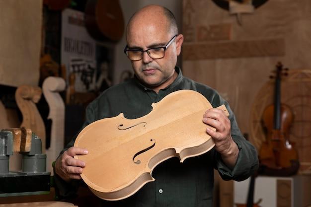 Homme fabriquant des instruments dans son atelier seul