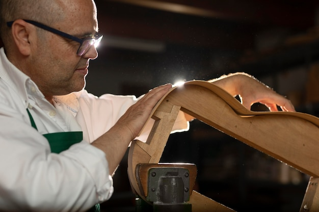 Homme fabriquant des instruments dans son atelier
