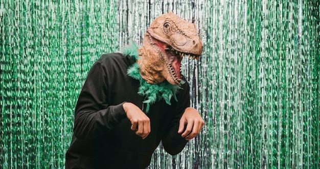 Homme faible angle en costume de dinosaure