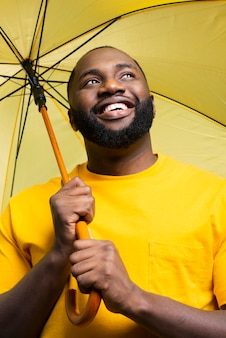 Homme faible angle avec parapluie