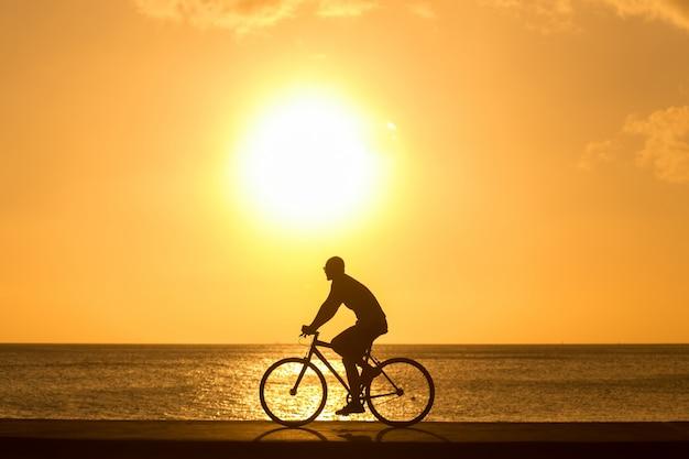 Homme faire du vélo à l'extérieur contre le coucher du soleil. silhouette.