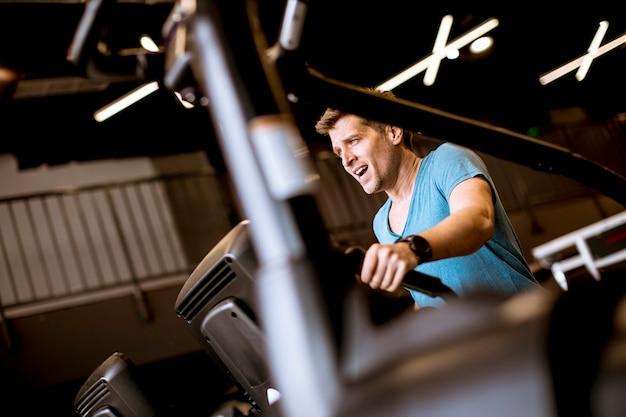 Homme, faire des exercices sur vélo elliptique dans le club de sport fitness gym