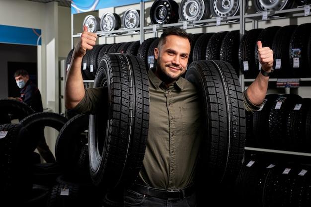 Homme faisant des achats dans un magasin d'accessoires de voiture, client agréable et satisfait dans des stands de vêtements décontractés tenant des pneus de voiture. portrait