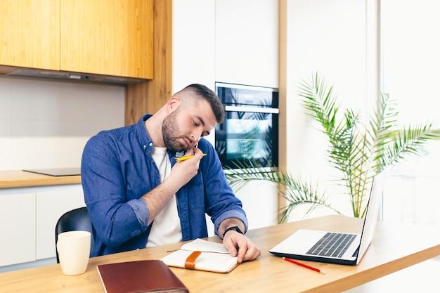 Homme faisant des affaires tout en restant à la maison assis dans la cuisine à la table et à l'aide d'un ordinateur portable