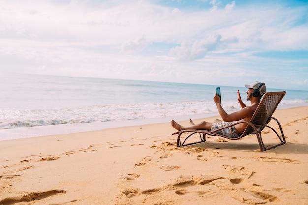 Homme faisant un appel vidéo en vacances d'été