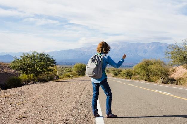 Homme faisant de l'auto-stop sur le bord de la route