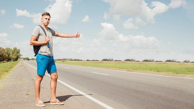 Homme faisant de l'auto-stop sur une route