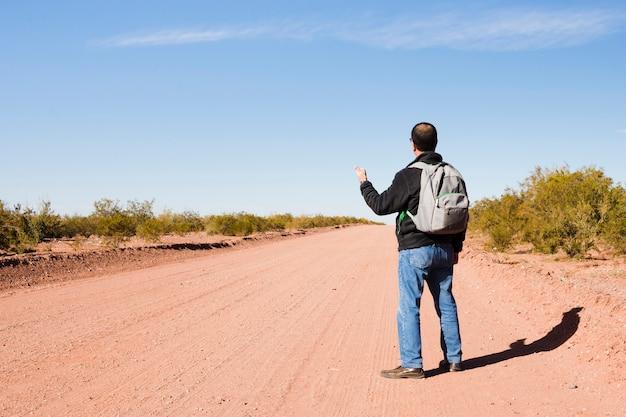 Homme faisant de l'auto-stop sur la route