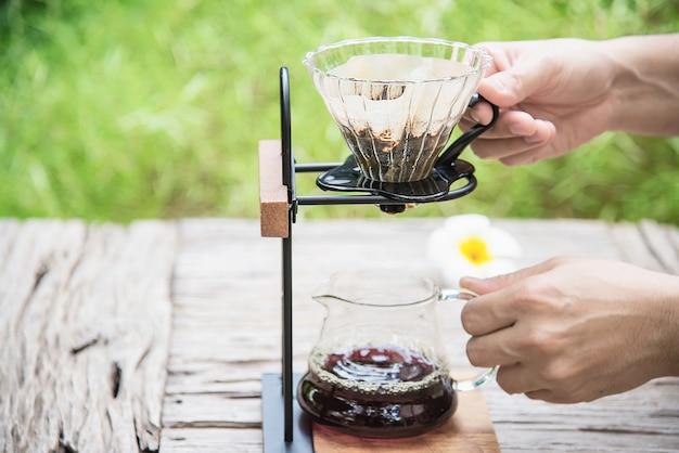 Homme faisant un café frais goutte à goutte dans un café vintage