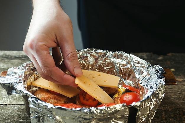 Homme faisant cuire le filet de poulet aux câpres, tomates et fromage.