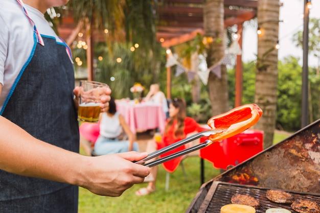 Homme faisant cuire des légumes et des hamburgers pour le dîner en plein air.