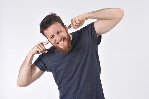 Homme faisant du bruit blessant ses oreilles sur blanc