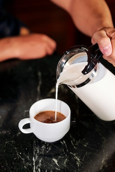 Homme faisant du café avec du lait
