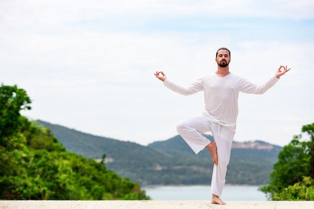 Homme faisant du yoga classique indien à la mer et aux montagnes