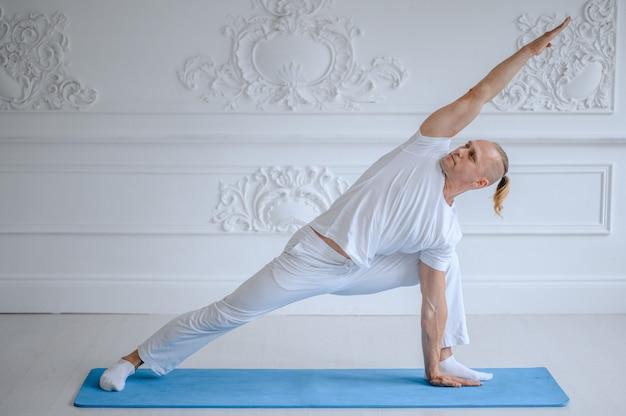 Homme faisant du yoga à la maison