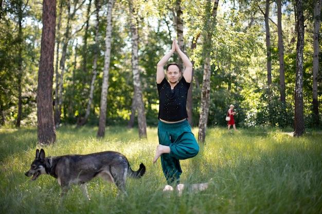 Homme faisant du yoga avec son chien dans le parc sur l'herbe. journée internationale du yoga