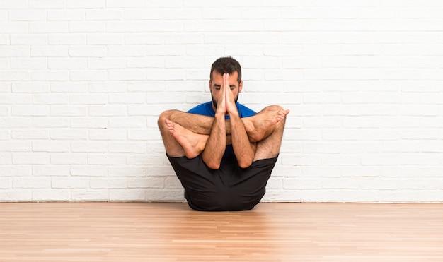 Homme faisant des exercices de yoga à l'intérieur