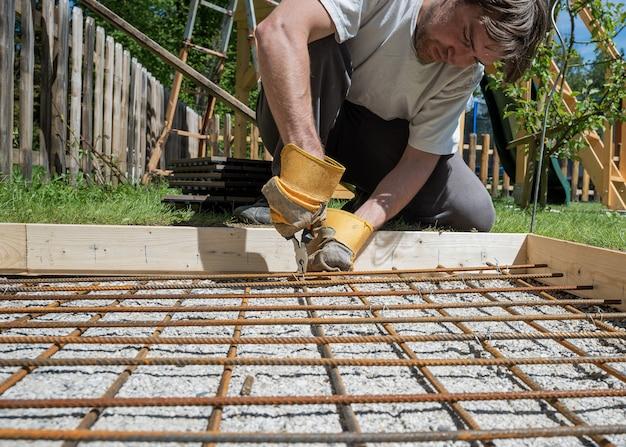 Homme faisant un filet de barres d'acier en les coupant avec un fil et une pince