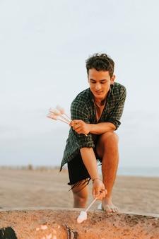 Homme faisant griller des guimauves sur un feu de joie
