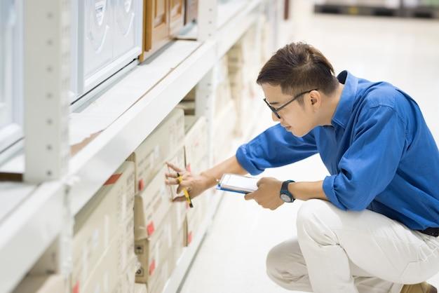 Homme faisant l'inventaire des produits dans des boîtes en carton sur des étagères