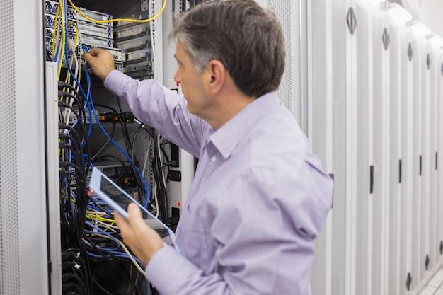 Homme faisant la maintenance du serveur avec tablette