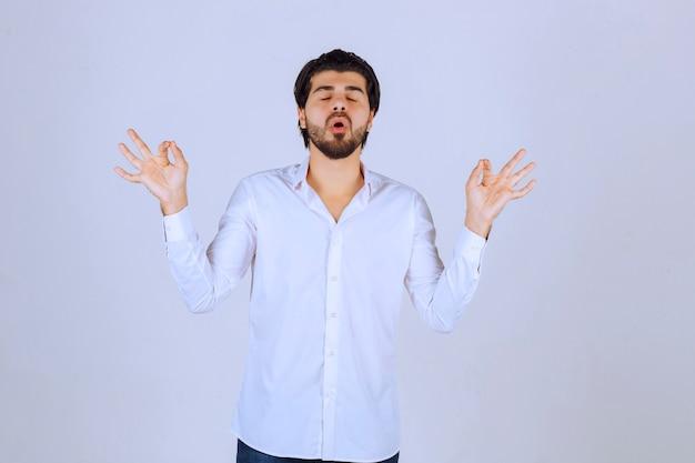 Homme faisant de la méditation et essayant de se calmer.