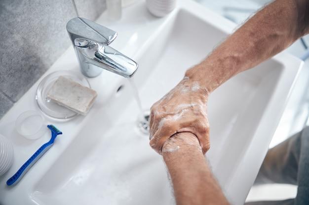 Homme faisant mousser le dos de sa main sur le lavabo