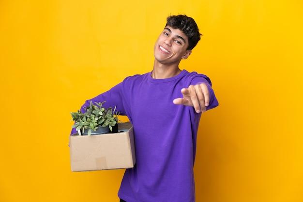 Homme faisant un mouvement tout en ramassant une boîte pleine de choses pointant vers l'avant avec une expression heureuse