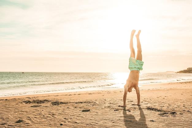 Homme faisant un poirier sur le sable de la plage au coucher du soleil seul - mode de vie sain et agréable en été