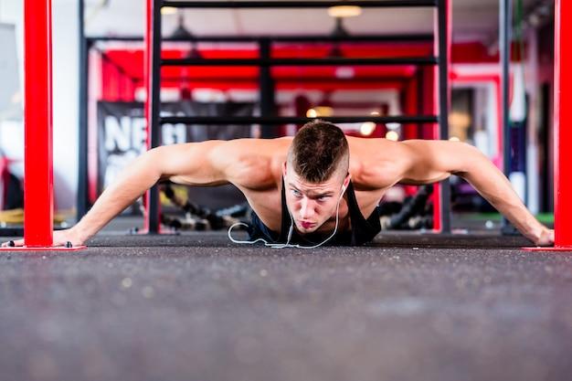 Homme faisant des pompes dans une salle de sport