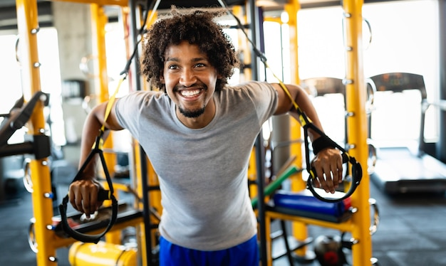 Homme faisant des pompes s'entraînant avec des sangles de fitness trx dans la salle de sport. concept de sport de mode de vie sain d'entraînement