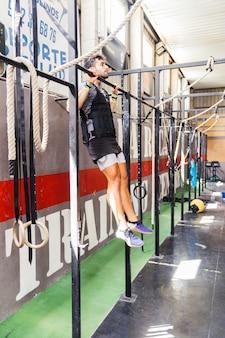 Homme faisant pull ups dans la salle de gym