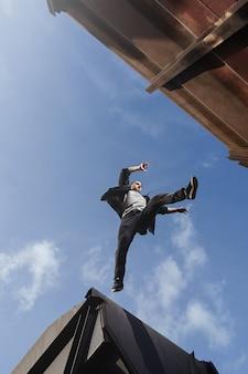 Homme faisant un saut effrayant entre les toits. guy pratiquant le parkour en course libre.