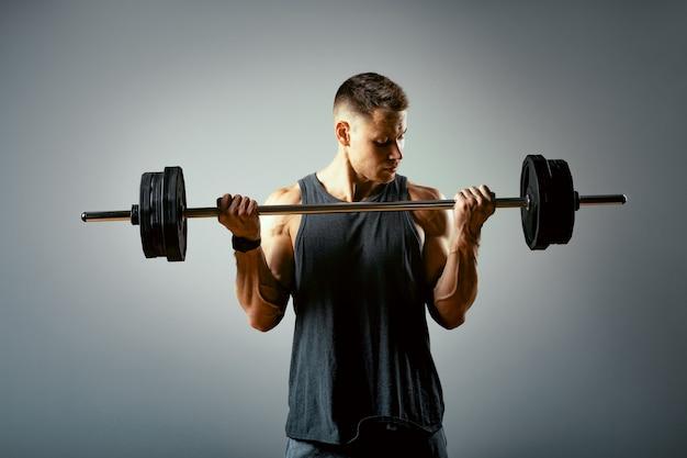 Homme faisant la séance d'entraînement arrière, ligne d'haltères en studio sur fond gris.