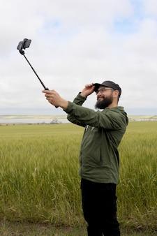 Un homme faisant selfie par smartphone en plein air dans le champ, style barbe hipster